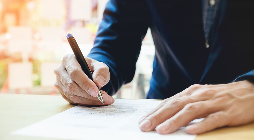 your guide to drafting business terms and conditions man signing terms and conditions of small business